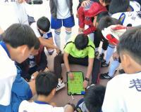 教练在场边用战术板指导小球员